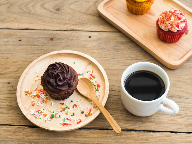 Neben cupcake haben vintage wecker und weiße kaffeetasse