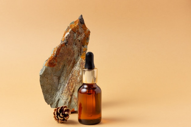 Neben dem stein steht eine bernsteinflasche für ätherische öle und kosmetika. glasflasche. tropfer, sprühflasche. naturkosmetik-konzept.