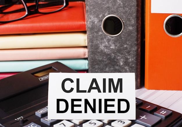 Neben den tagebüchern und ordnern mit dokumenten auf dem taschenrechner befindet sich eine weiße karte mit der aufschrift claim denied