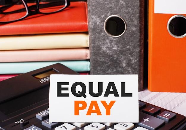 Neben den tagebüchern und ordnern mit dokumenten auf dem taschenrechner befindet sich eine weiße karte mit der aufschrift equal pay