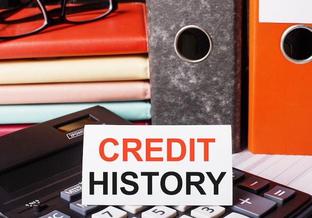 Neben den tagebüchern und ordnern mit dokumenten auf dem taschenrechner befindet sich eine weiße karte mit der aufschrift kreditgeschichte