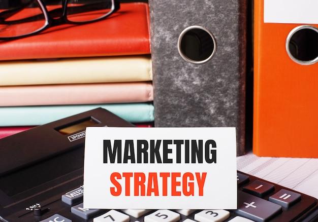 Neben den tagebüchern und ordnern mit dokumenten auf dem taschenrechner befindet sich eine weiße karte mit der aufschrift marketing strategy