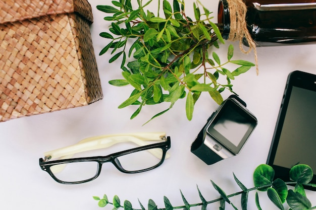 Neben einer grünen pflanze liegen eine telefonbrille und elektronische uhren