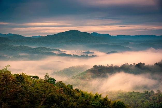 Neblig in den bergen mit dramatischem himmel bei sonnenaufgang