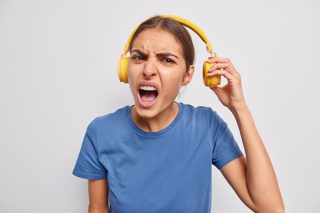 Negativ frustrierte europäerin nimmt kopfhörer ab hört musik mit lautem ton entfernt kopfhörer, um tinnitus zu vermeiden, trägt lässiges blaues t-shirt isoliert über grauer wand