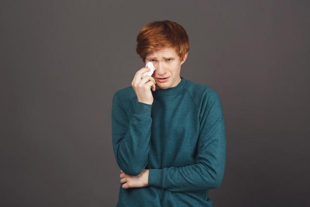 Negative emotionen. dunkle wand. porträt des jungen schönen unglücklichen jugendlichen kerls im grünen pullover, der weint, wischt tränen mit papierservietten ab, verärgert, weil schlechte ergebnisse im wettbewerb.