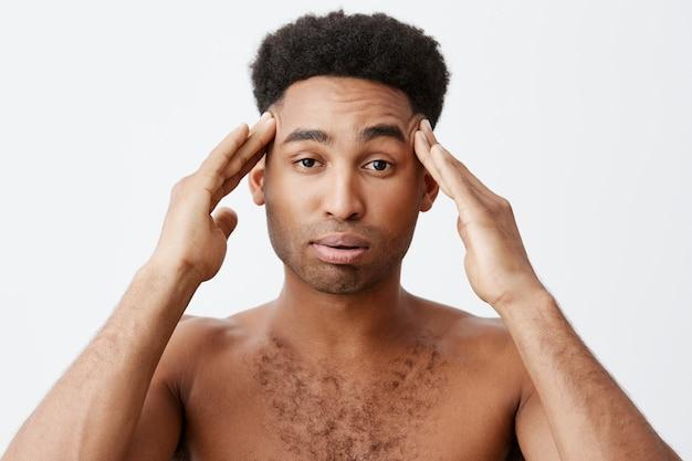 Negative emotionen. mann, der kopfschmerzen hat, nachdem er die ganze nacht gefeiert hat. nahaufnahme des jungen dunkelhäutigen mannes mit afro-frisur ohne kleidung, die den kopf mit den händen massiert.