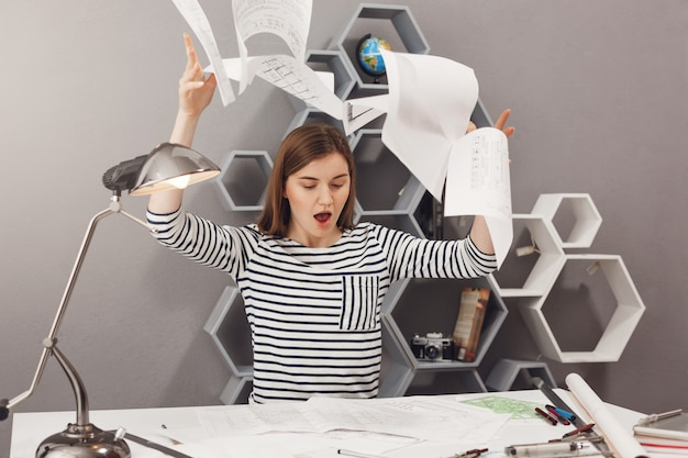 Negative emotionen. porträt einer wütenden jungen, gut aussehenden architektin, die papiere wegwirft und nach vielen versuchen wütend auf das schlechte ergebnis der arbeit ist.