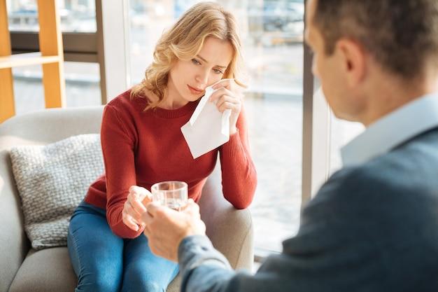 Negative emotionen. unglückliche freudlose traurige frau, die ein papiertaschentuch hält und ihre tränen wegwischt, während sie an depressionen leidet