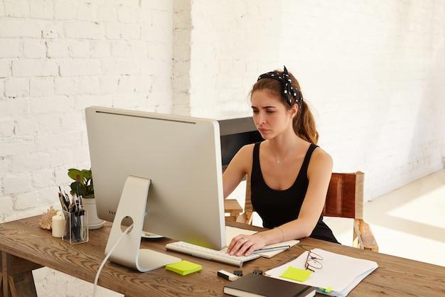 Negative menschliche emotionen. die verärgerte frau schaut auf den bildschirm, der am schreibtisch vor dem computer im modernen büro arbeitet. müder designer oder architekt, der am schreibtisch arbeitet