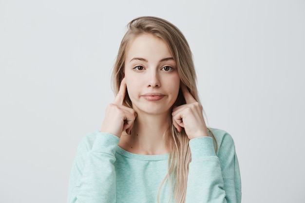 Negative menschliche emotionen, reaktionen und einstellungen. frustrierte genervte frau mit blond gefärbtem haar, die ohren mit den fingern verstopft, sich durch lautes nerviges geräusch gereizt fühlt, kann sich nicht auf die arbeit konzentrieren