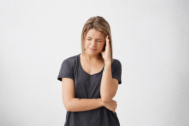 Negative menschliche emotionen und gefühle. unglückliche junge frau, die unter starken kopfschmerzen oder migräne leidet
