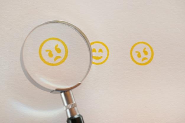 Negative rückmeldung. gelber smiley im vergrößerungsglas