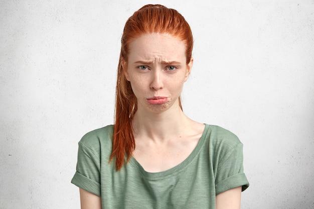 Negatives emotionskonzept. schöne rothaarige studentin krümmt die lippen und wird weinen, hat wichtige prüfung nicht bestanden, hat probleme.
