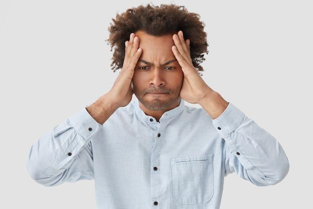 Negatives gesichtsausdruckkonzept. der gestresste afroamerikaner hält die hände auf dem kopf, drückt die lippen und schaut verzweifelt nach unten. er trägt ein elegantes hemd, ist in panik und leidet unter kopfschmerzen
