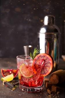 Negroni-cocktail, das auf dem steinhintergrund steht und mit würfeln des braunen zuckers gedient wird