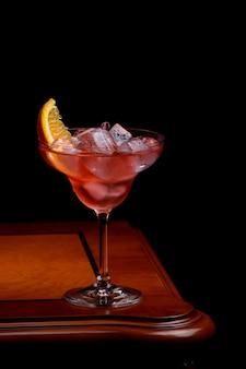 Negroni-cocktail mit orangenscheibe auf klassischem altmodischem holztisch