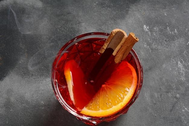 Negroni cocktail. rauchiger italienischer aperitivo mit gin, campari, martini rosso, orange und eiswürfeln, serviert in glas auf dunkler steinoberfläche