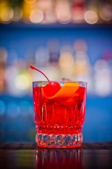 Negroni. roter getränkecocktail im glas mit kirsch- und orangenschale mit bokeh-effekt.