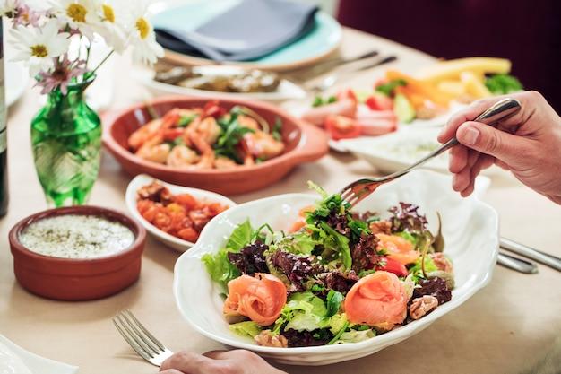 Nehmen des grünen salats von der weißen schüssel mit gabel.