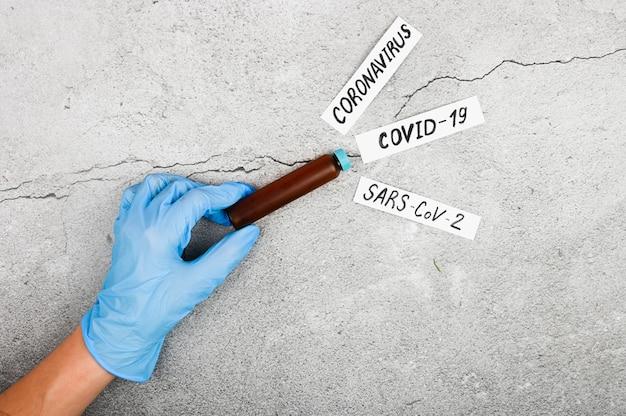 Nehmen sie blut, um den coronavrus zu bestimmen. der arzt führt einen biochemischen bluttest durch, um das coronavirus nachzuweisen. nahansicht. auf einem schwarzen hintergrund. das konzept des coronavirus.