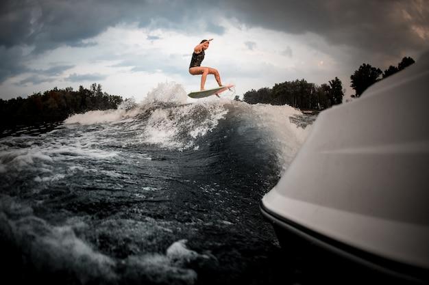 Nehmen sie das sitzmädchen ab, das auf das wakeboard auf dem fluss auf der welle des motorboots springt
