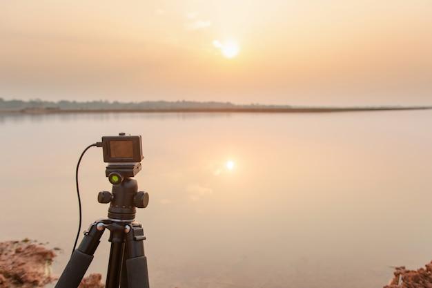 Nehmen sie den sonnenuntergang am fluss mit der action-kamera auf einem stativ auf