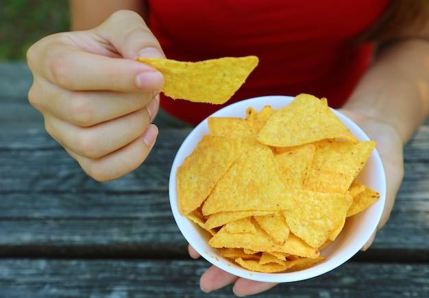 Nehmen sie den tortilla-chip von hand aus einer vollen schüssel.