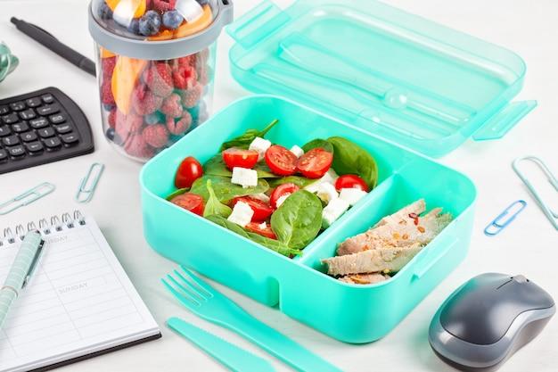 Nehmen sie die brotdose mit frischem salat und thunfisch über den schreibtisch mit büromaterial.