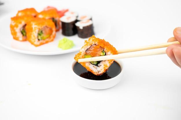 Nehmen sie ein kalifornisches maki-brötchen mit bambus-essstäbchen und geben sie es in sojasauce. rosa ingwer, wasabi. asiatisches essen, japanischer küchenhintergrund