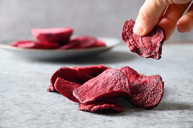 Nehmen sie ein stück gemüse-rote-bete-chips auf grauem hintergrund