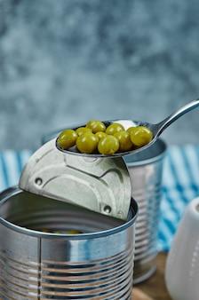 Nehmen sie einen löffel gekochte grüne erbsen aus der blechdose. Kostenlose Fotos