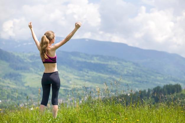 Nehmen sie junge frau mit den angehobenen armen draußen auf hintergrund der schönen berglandschaft am sonnigen sommertag ab.