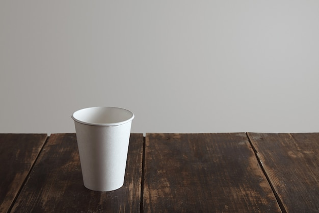 Nehmen sie leeres papierglas allein auf gealtertem gebürstetem holztisch weg, lokalisiert auf weißem hintergrund