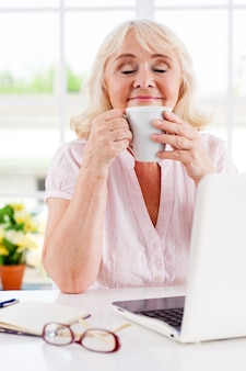 Nehmen sie sich einen moment zeit, um sich zu entspannen. fröhliche ältere frau, die eine tasse hält und die augen geschlossen hält, während sie an ihrem arbeitsplatz sitzt