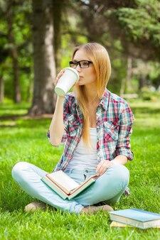 Nehmen sie sich zeit für eine kaffeepause. schöne junge studentin, die kaffee trinkt, während sie in einem park mit büchern um sie herum sitzt