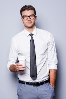 Nehmen sie sich zeit für eine kaffeepause. selbstbewusster junger mann in hemd und krawatte mit kaffeetasse und blick in die kamera, während er vor grauem hintergrund steht
