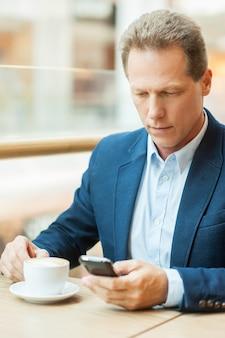 Nehmen sie sich zeit für eine kaffeepause. selbstbewusster reifer mann in abendkleidung, der kaffee trinkt und eine nachricht auf dem handy eingibt, während er im restaurant sitzt