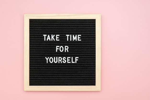 Nehmen sie sich zeit für sich. motivationszitat auf briefbrett auf rosa hintergrund. draufsicht flat lay kopierraum