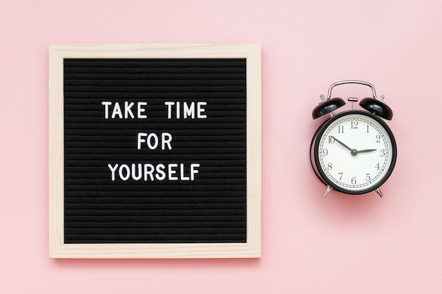 Nehmen sie sich zeit für sich. motivzitat auf briefpapier und schwarzem wecker auf rosa