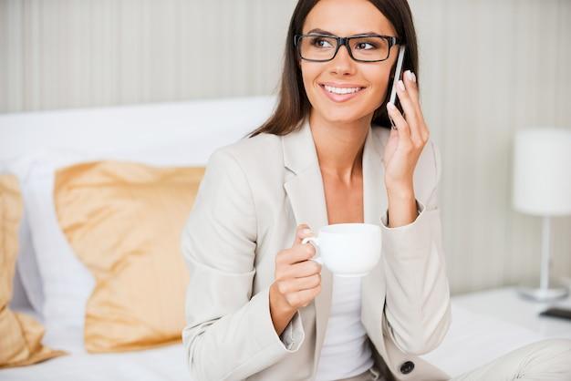 Nehmen sie sich zeit, um mit dem nächsten zu sprechen. schöne junge lächelnde geschäftsfrau im anzug, die kaffee trinkt und mit dem handy spricht, während sie auf dem bett im hotelzimmer sitzt?