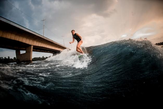 Nehmen sie sitzmädchenreiten auf dem wakeboard auf dem fluss im hintergrund der brücke ab