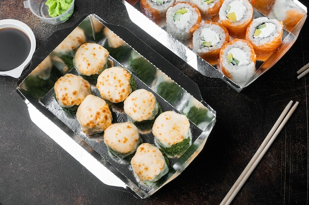 Nehmen sie sushi-rollen in behältern, philadelphia-rollen und gebackenen garnelen-rollen auf altem, dunklem rustikal mit