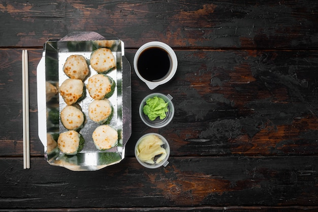Nehmen sie sushi-rollen in behältern, philadelphia-rollen und gebackenen garnelen-rollen auf einem alten dunklen holztisch mit