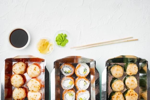 Nehmen sie sushi-rollen in behältern, philadelphia-rollen und gebackenen garnelen-rollen auf weißem stein mit