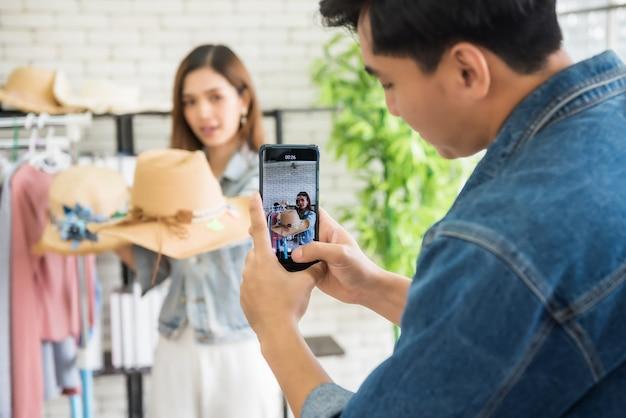 Nehmen sie video-streaming online per smartphone von beauty-blogger oder stylist beliebtes influencer-mädchen auf, das modehut verkauft. meinungsführer-trend auf ihrem online-blog-kanal.