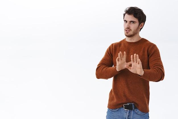 Nein danke. widerstrebender und unzufriedener junger gutaussehender mann tritt zurück, verzieht das gesicht vor abneigung und abneigung und schüttelt hände in nein