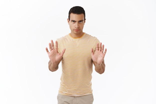 Nein, ich will nicht. ernsthaft aussehender selbstbewusster und entschlossener hispanischer junger männlicher mann, der eine stoppgeste macht making