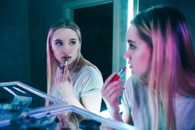 Nein zu drogen. porträt der jungen schönen frau, die ihre lippen mit rotem lippenstift nahe kokainlinien in der toilette des nachtclubs anwendet. sie schaut in den spiegel. gesunder lebensstil oder drogenzusatz