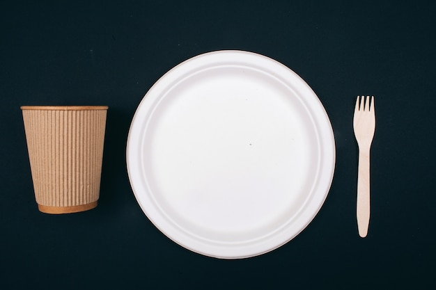 Nein zu plastik. hölzerne umweltfreundliche pappteller, tasse und gabel auf dunklem hintergrund, draufsicht. zeit etwas zu ändern. neue regeln zur reduzierung von plastikmüll, eu-richtlinie. einwegkunststoff verbieten.